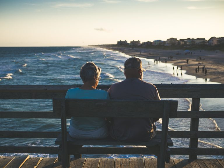 man and woman sitting on bench in front of beach
